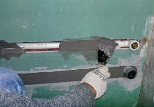 Прячем трубы в стену затем шпаклюем цементом