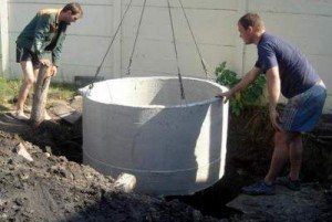 Процесс установки бетонных колец в выгребную яму
