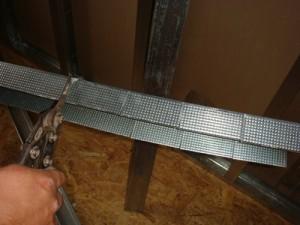 Отрезаем ножницами металлический профиль для крепления гипсокартона