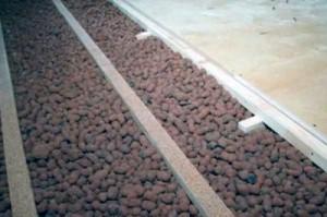 Выравниванием и утеплением пола с использованием керамзита и цементно-песчаного раствора.