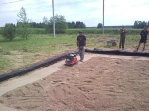Площадку под фундамент засыпают песком и трамбуют
