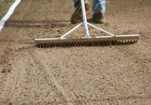 Процесс рыхления почвы граблями