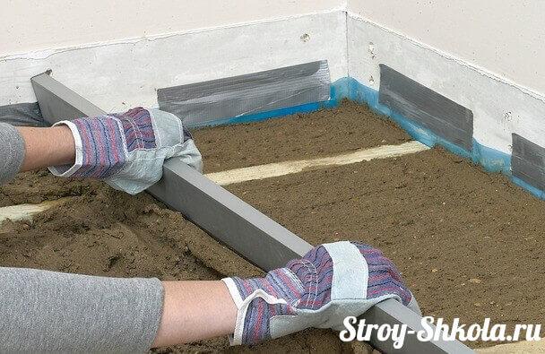 Процесс выравнивания цементной стяжки с помощью правила