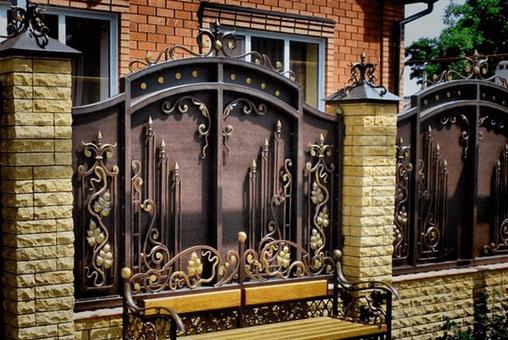 Металлический забор в оправе из рельефного кирпича выглядит восхитительно.