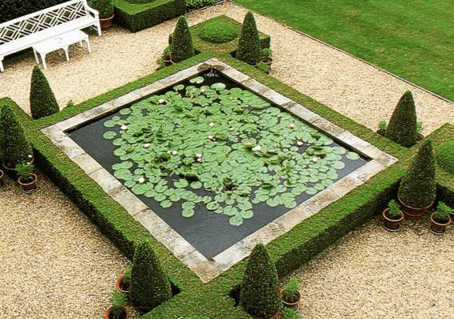 Формальный пруд украшенный густой растительностью