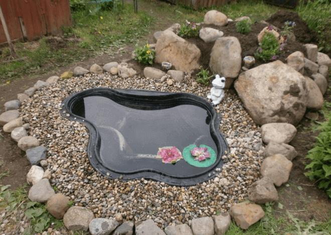 Пруд из готовой пластиковой формы, оформленный камнями.