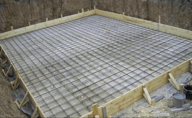 Плитный фундамент на дне котлована с уложенной арматурой.