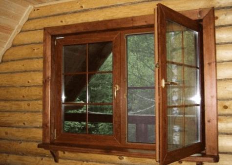 Коричневое пластиковое окно в новом деревянном доме.