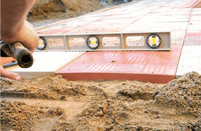 Выравнивание с помощью уровня и резинового молотка тротуарной плитки