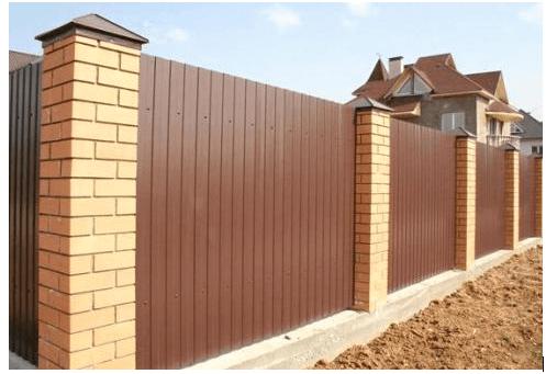 Типичный забор из профнастила с кирпичными столбиками – идеальное решение для широкого потребления